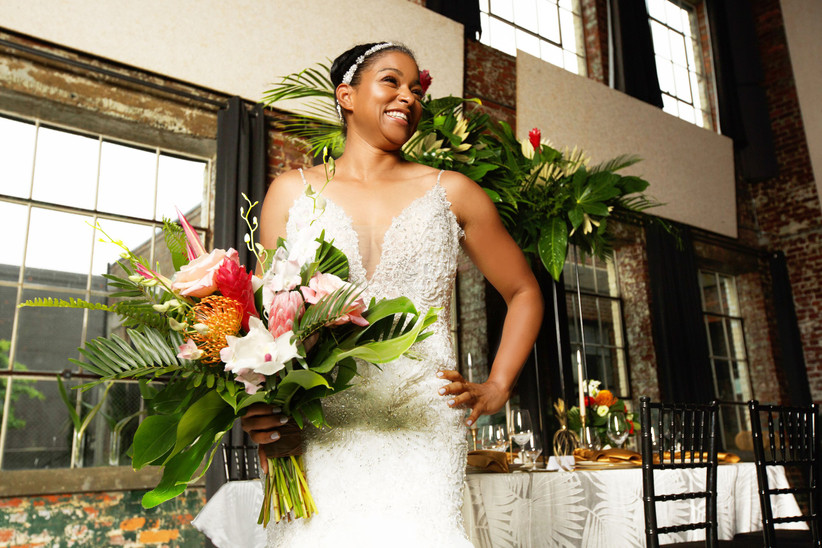 bride holds protea bouquet with ginger torch, palm leaves, and orchids