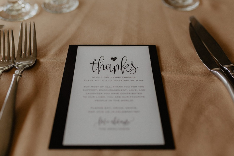 wedding thank you card is displayed at guest's reception table setting