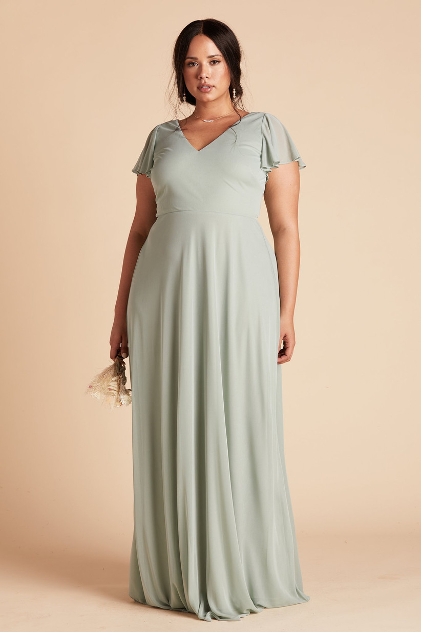 Model wearing simple sage green pastel bridesmaid dress with flowy chiffon skirt and short sleeves