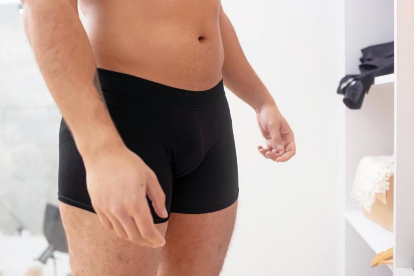 Close-up of man's lower half wearing snug black trunks