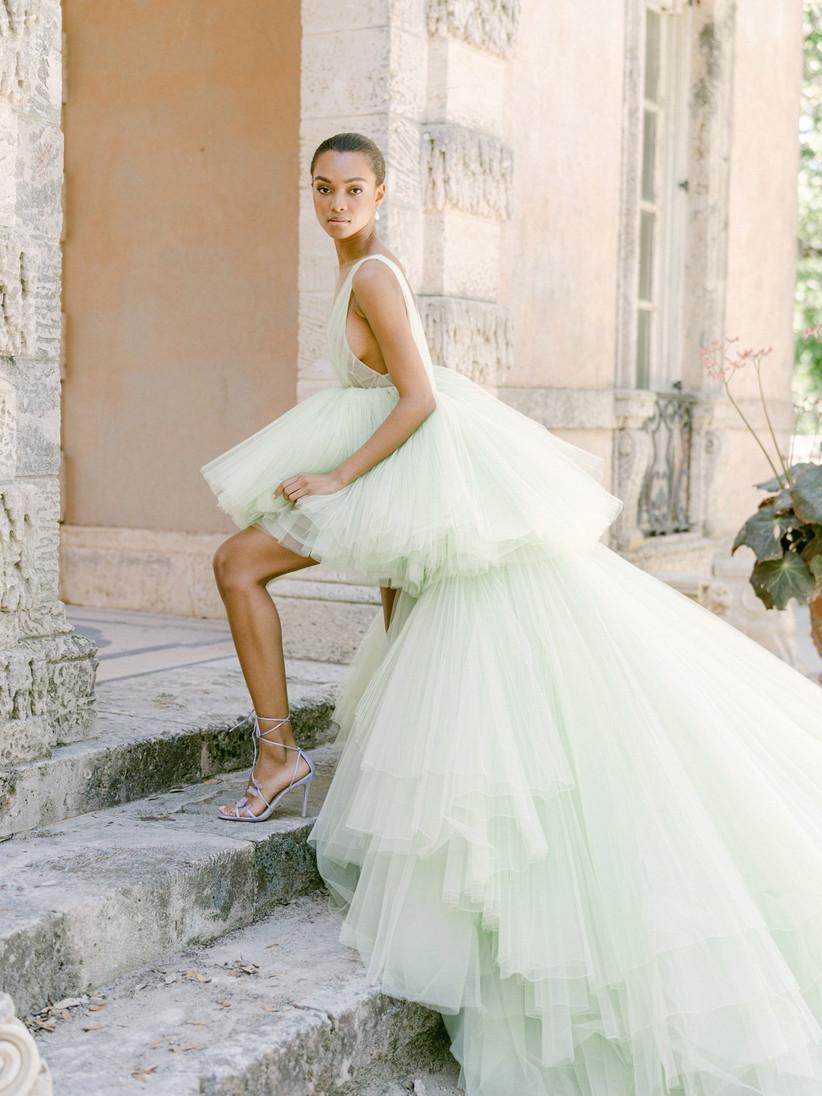 bride wearing pale green tulle wedding dress walks up a flight of steps outside