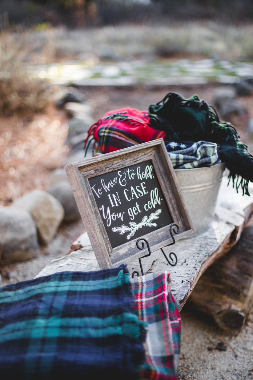 stack of plaid fleece blankets next to chalkboard wedding sign that reads