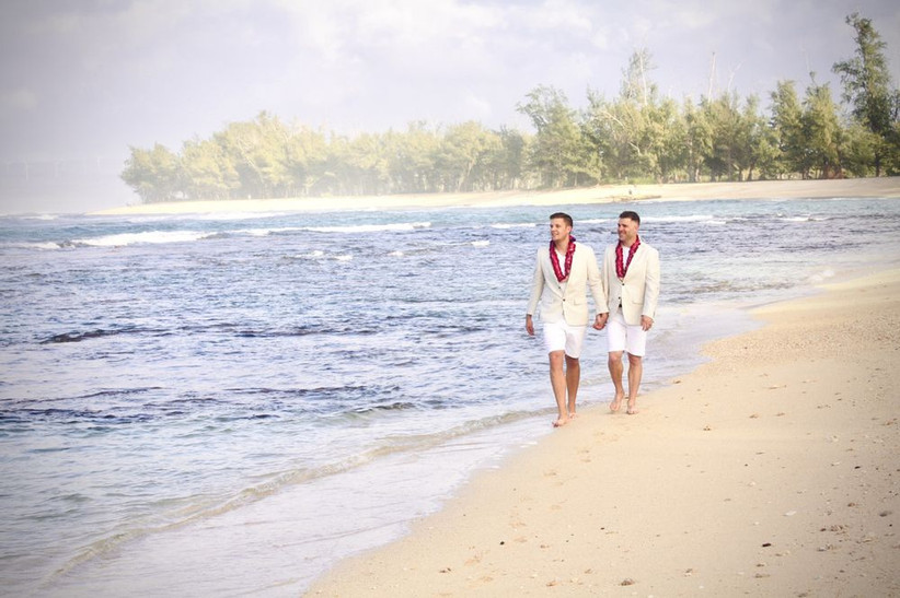 LGBTQ+ couple two grooms walking on the beach wearing shorts and matching pink flower leis