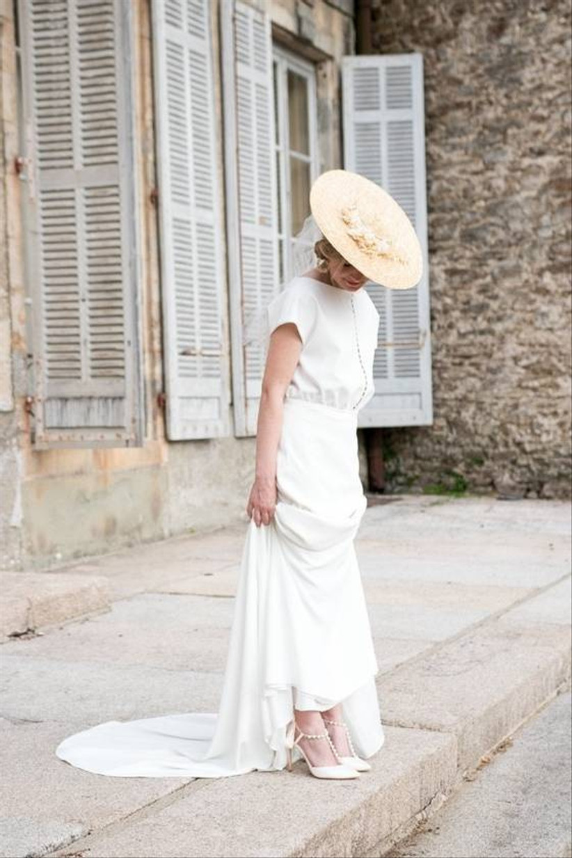 bride stands outside wearing wedding dress and flat straw hat with white flowers