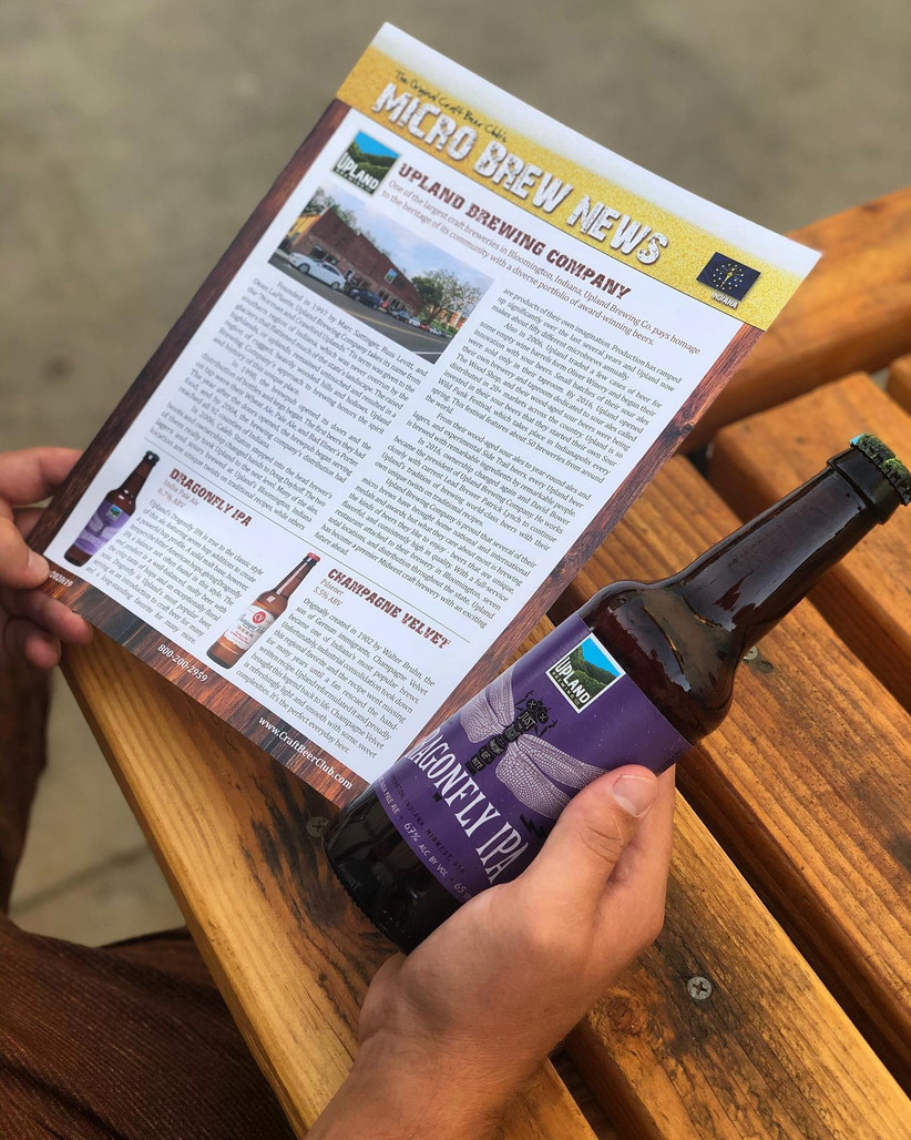 Close up of man holding bottle of craft beer in one hand and Beer Club newsletter in the other