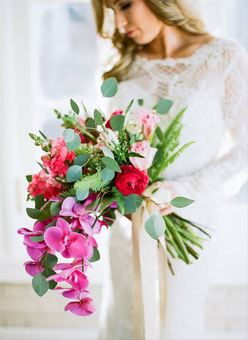 colorful beach wedding bouquet with greenery and bright pink phalaenopsis orchids cascading down the front