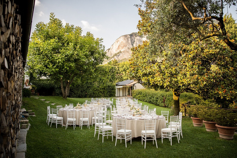 outdoor reception at italy wedding venue shaded garden surrounded by trees and hillside views