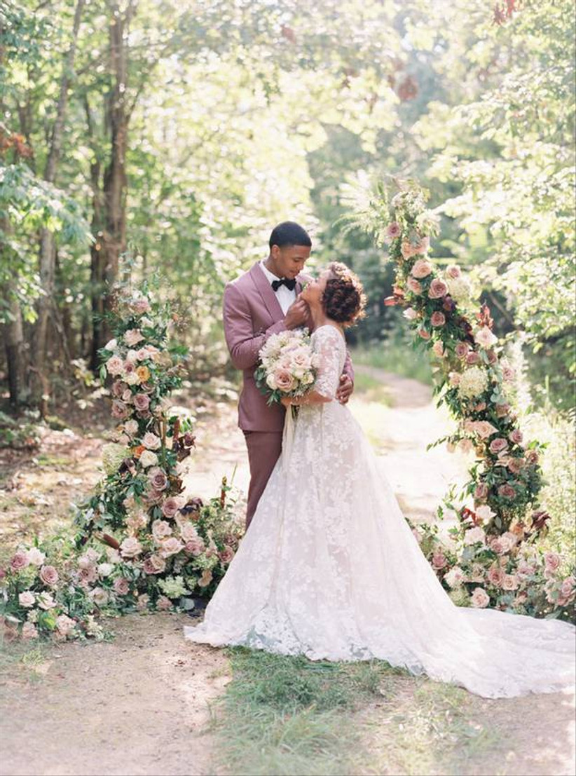 Black bride and groom pose outside in front of oversized floral arch