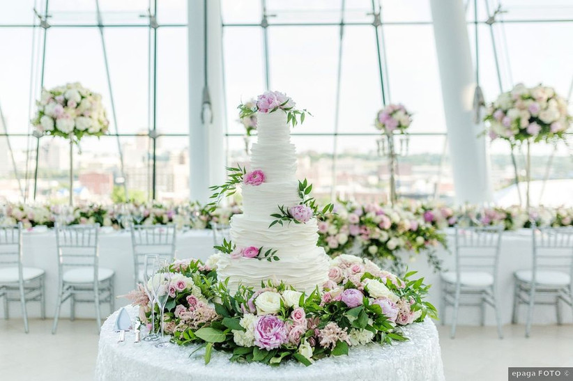 tall wedding cake surrounded by flowers on a table