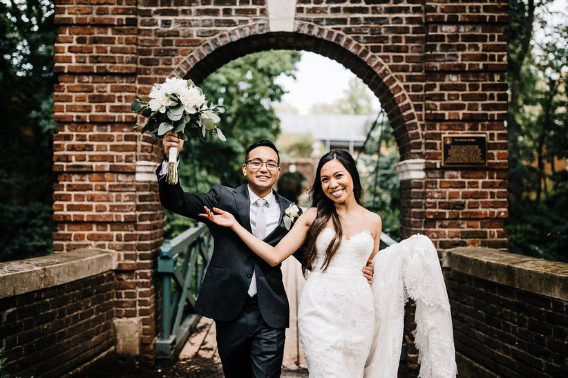 Bride and groom walk under a brick archway while smiling for the camera. he is carrying her bouquet, which includes white flowers and eucalyptus
