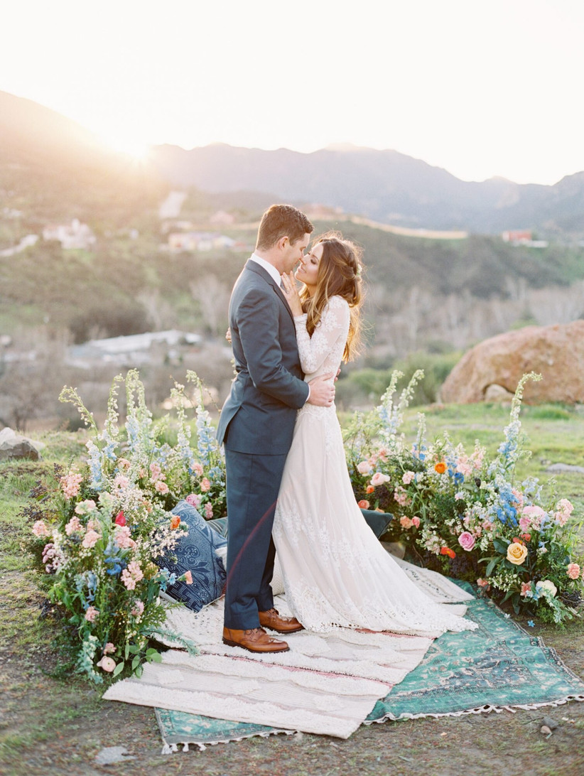 boho wedding arch backdrop with tall blue delphinium and orange poppies