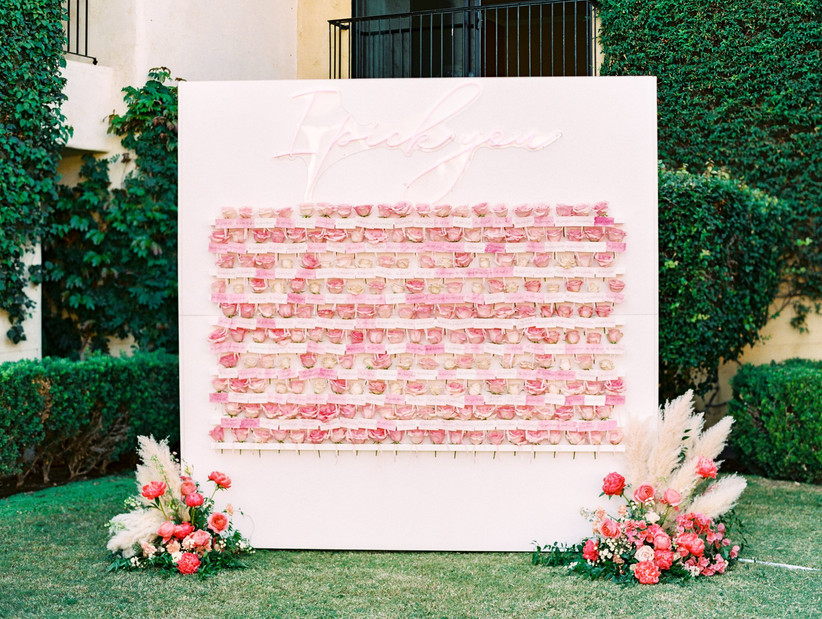 creative wedding escort card idea flower wall with individual roses and neon sign on the top that says