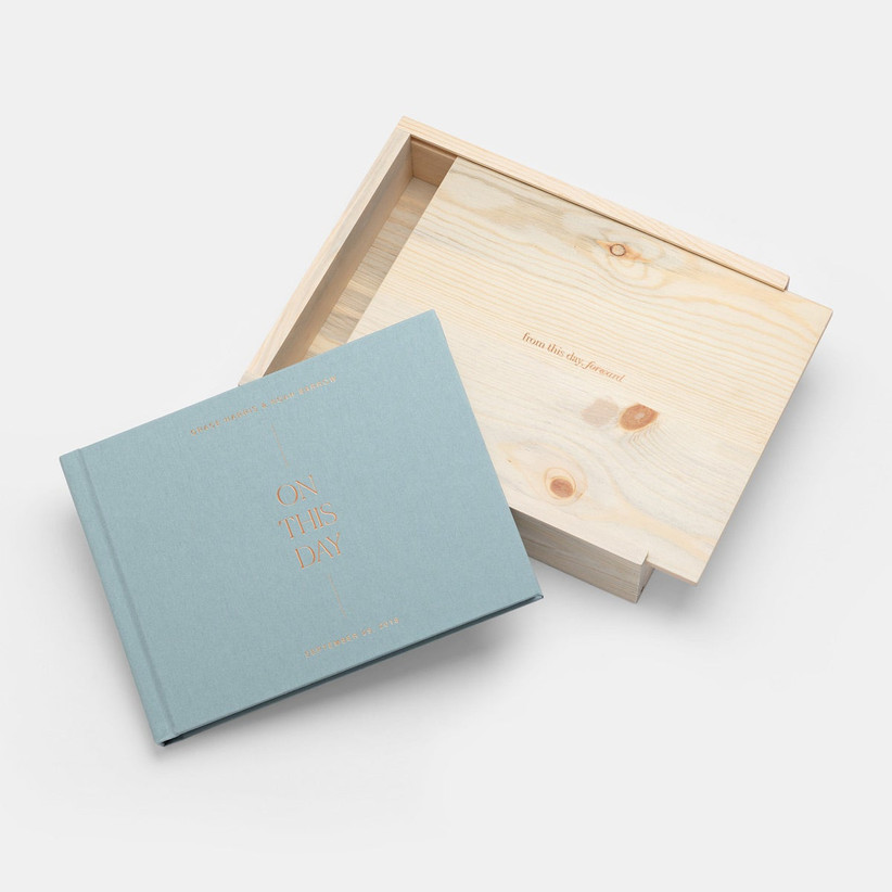 Blue foil-stamped wedding photo book with On This Day in gold foil next to wooden keepsake box