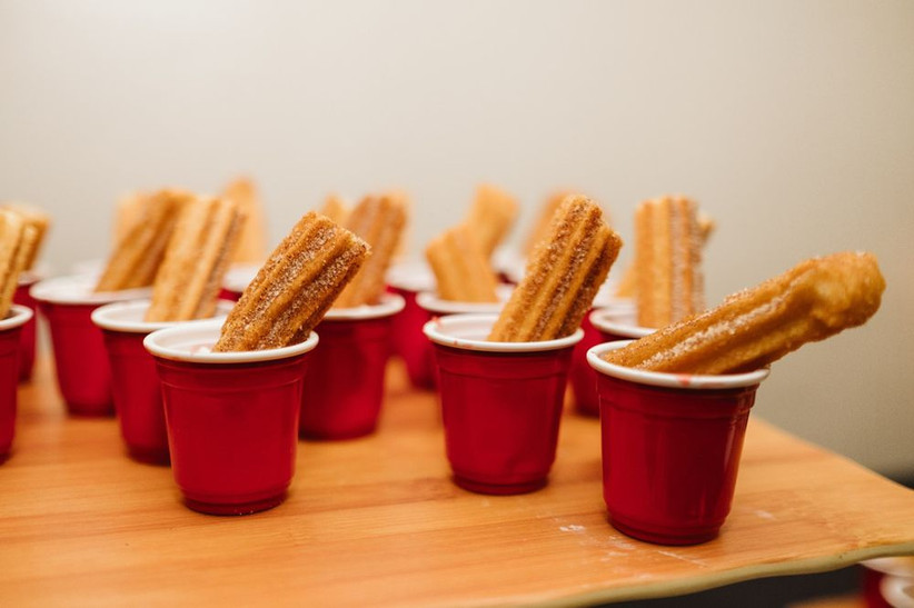 churros in mini red cups with dipping sauce
