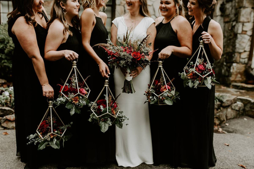 bridesmaids stand next to bride holding geometric lanterns filled with flowers as bouquets