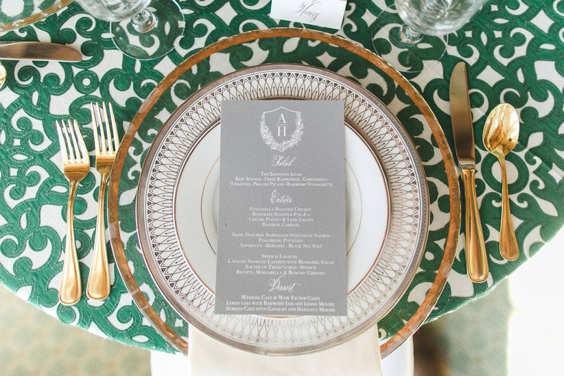 photo of place setting from above set on patterned green and white tablecloth with gold flatware and gold-rimmed plates