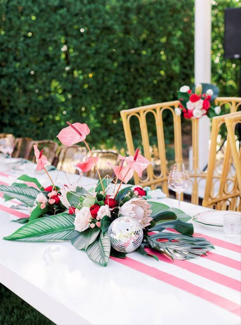 modern tropical beach wedding centerpiece pink anthurium and magenta ranunculus with proteas and miniature disco balls on pink and white striped tablecloth
