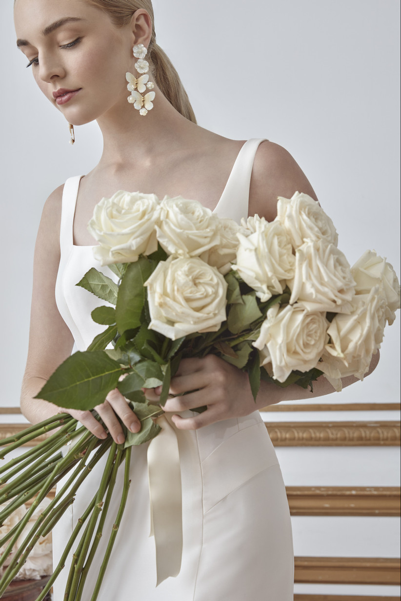 bride holds a bouquet of white long stem roses
