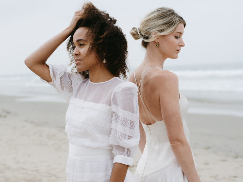 Two models on a beach wearing upcycled vintage wedding dresses