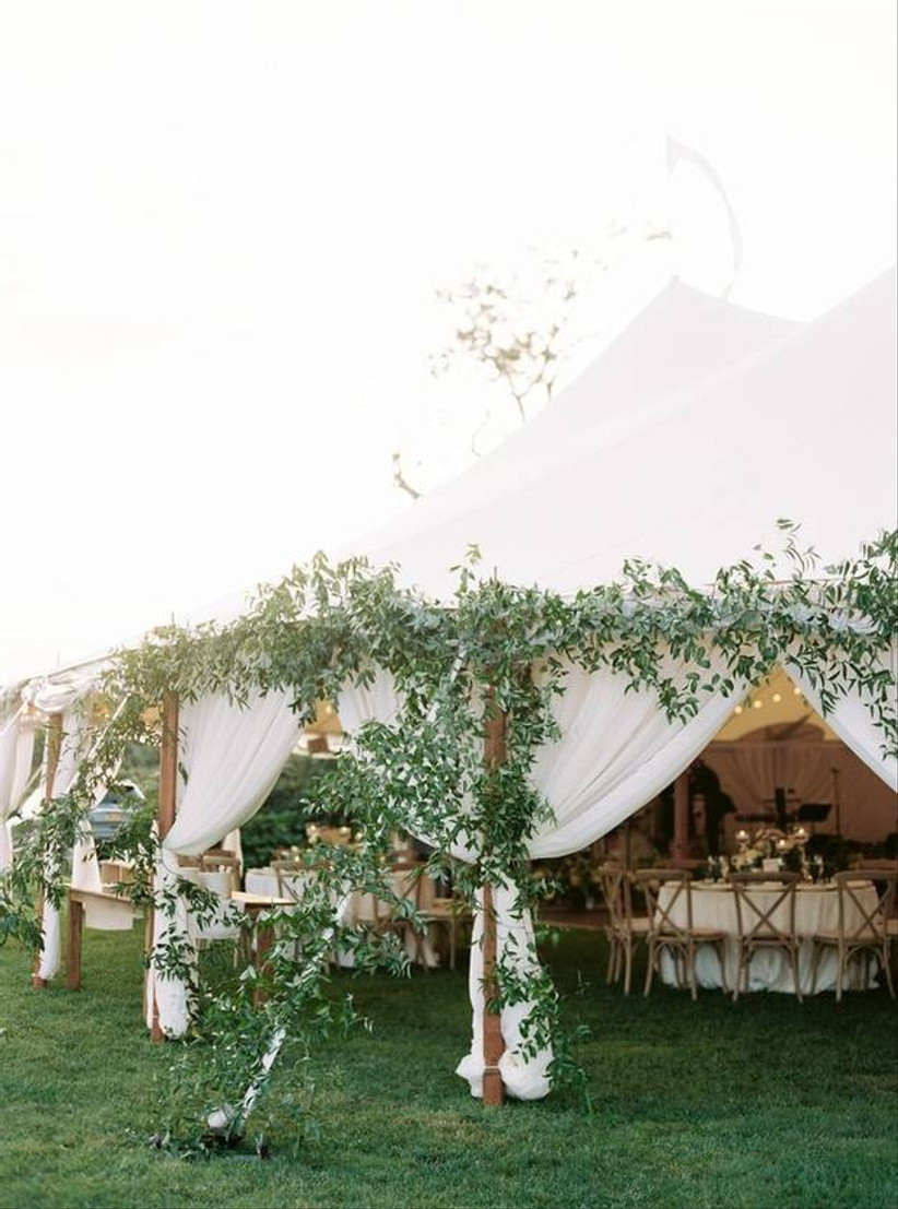 sailcloth wedding tent is decorated with greenery trailing up the posts and ropes