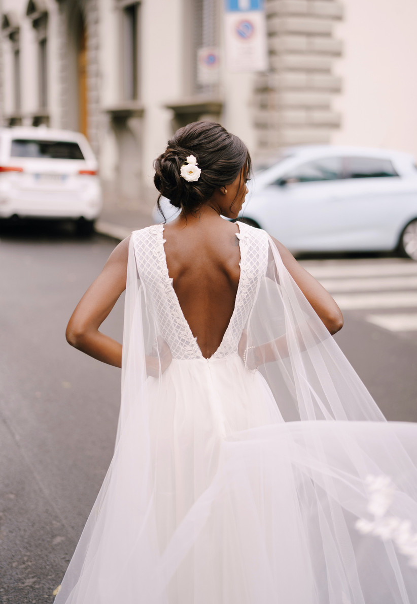 Black bride stands with her back to the camera on European street. she is wearing her hair up in a tousled low bun with a flower