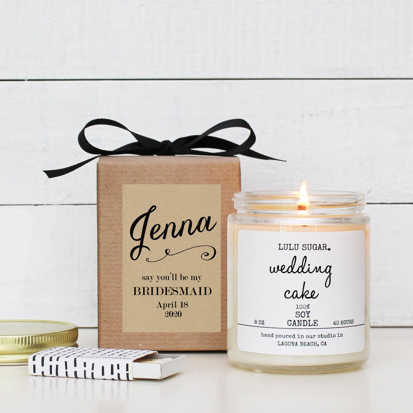 Wedding cake-scented candle next to pretty cardboard gift box with personalized bridesmaid proposal label and black bow