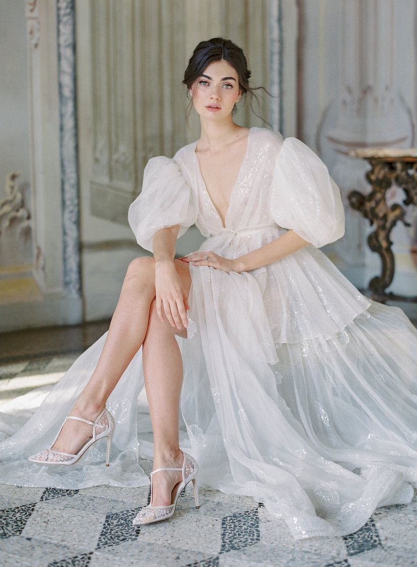 model sits with her legs crossed while wearing sheer puff-sleeve tulle wedding dress with sequins and lace appliques