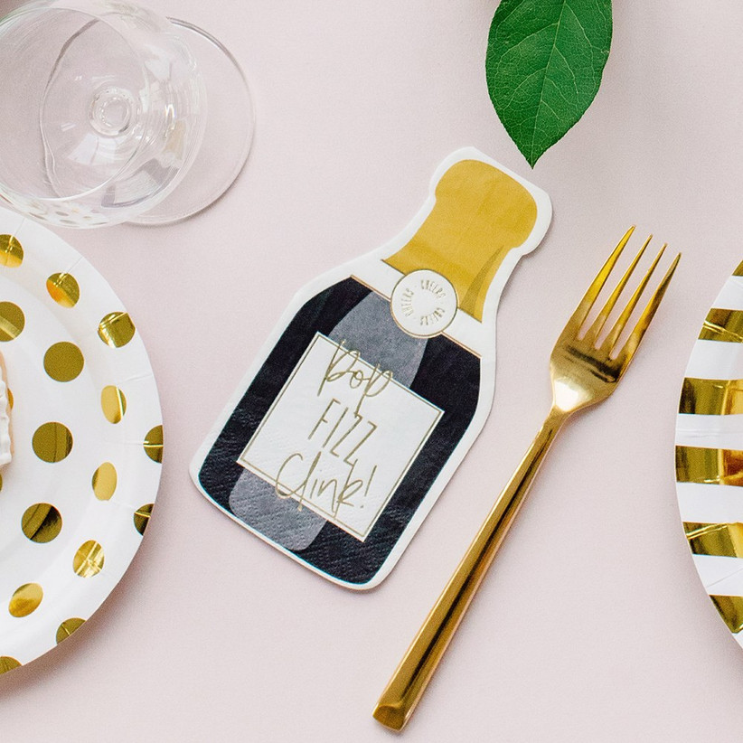Metallic gold and white theme tablescape with champagne-bottle shaped napkins reading Pop Fizz Clink