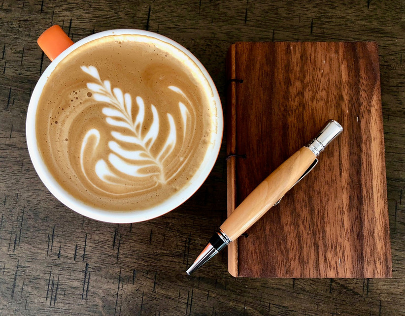 Wooden willow pen pictured next to a cup of coffee on top of a notebook