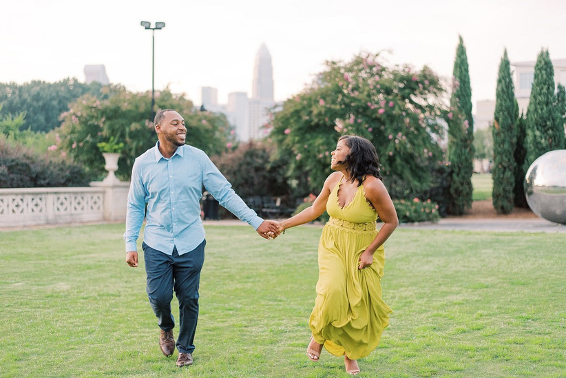 Black couple holds hands as they run through a manicured lawn. She is wearing a long lime green dress and he is wearing a blue button-down shirt