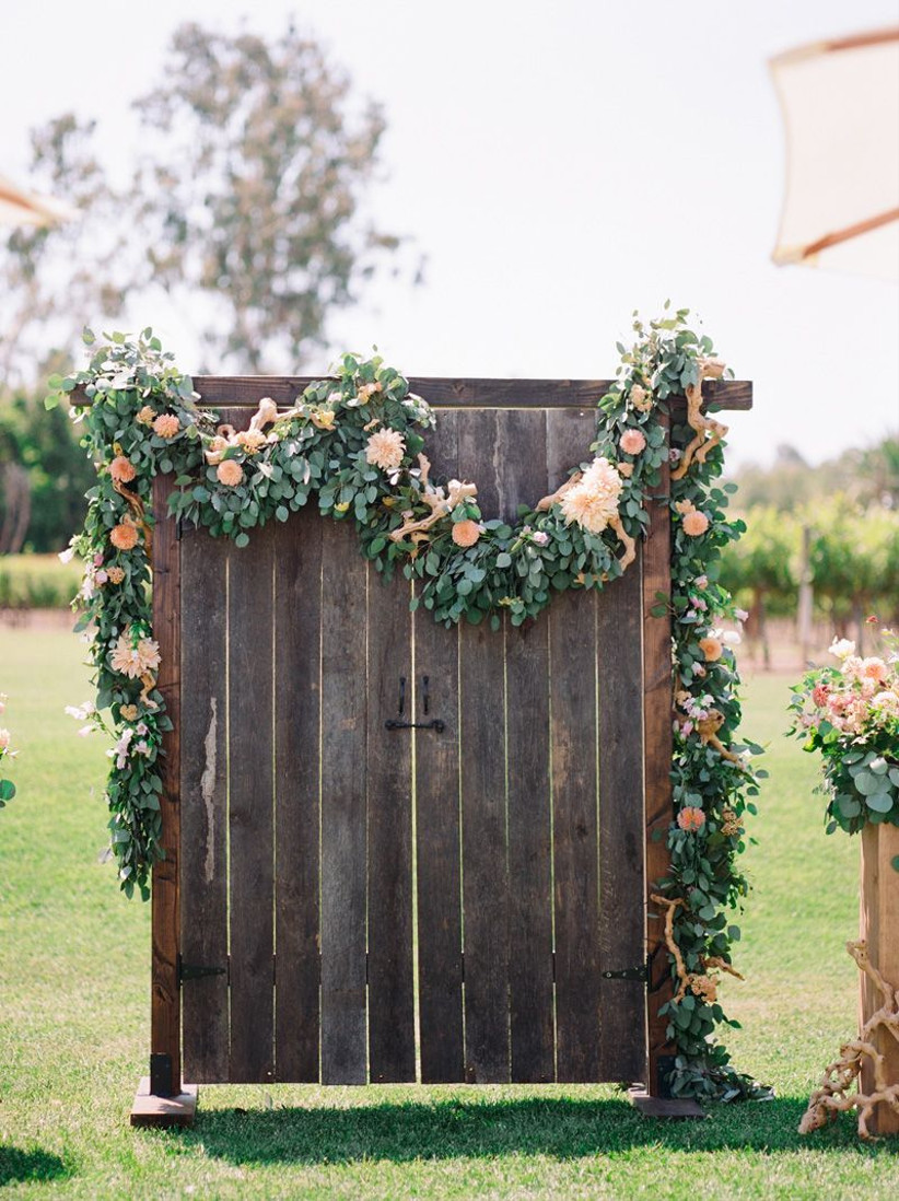 rustic wedding backdrop made from reclaimed wood door decorated with greenery and dahlia garland