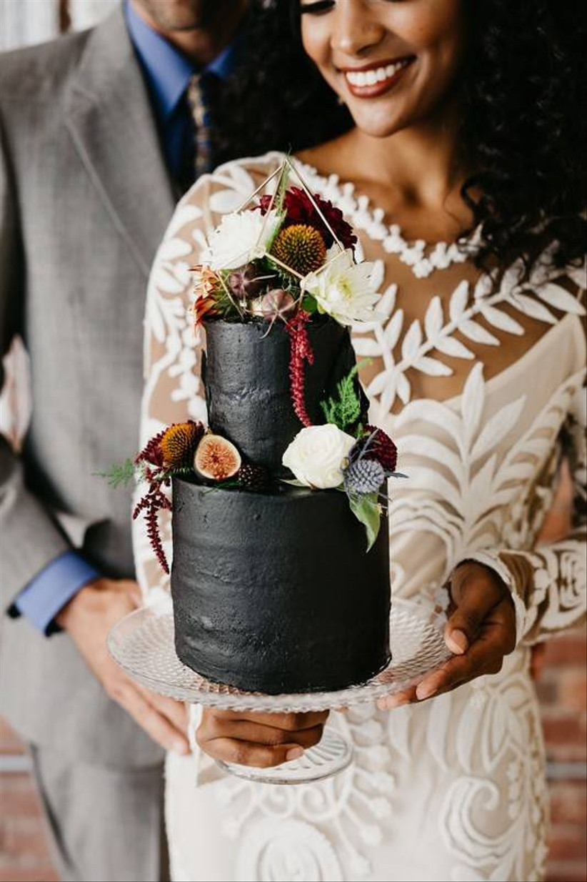 black wedding cake decorated with halved figs, white roses, and blue thistle