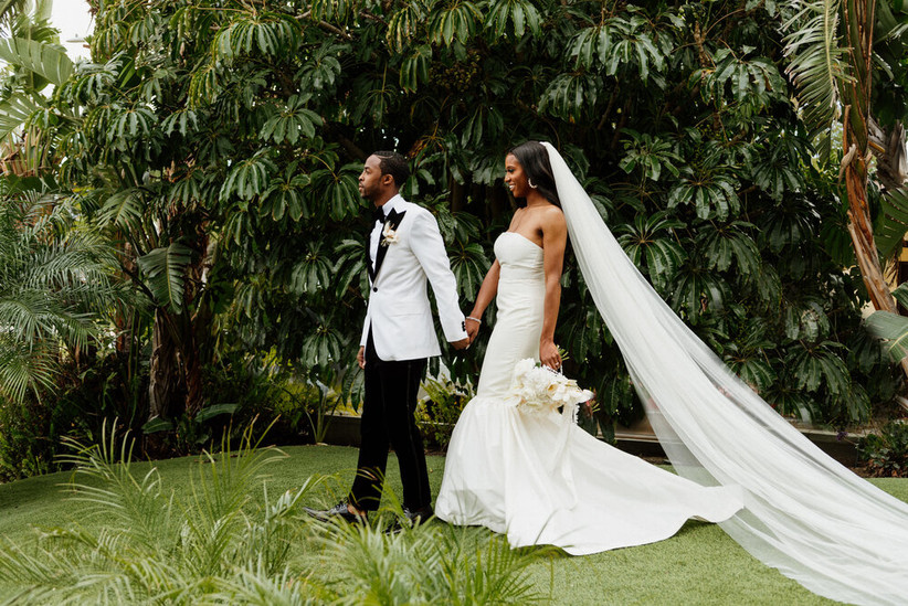 bride wearing cathedral-length veil holds groom's hand as they walk through a garden