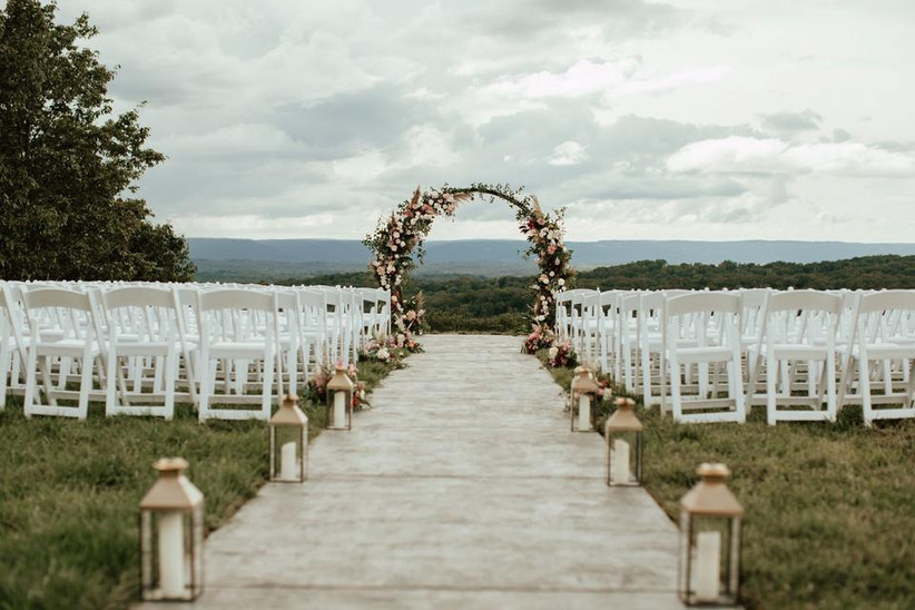 outdoor wedding aisle decor with white pillar candles in glass and wooden lanterns along the aisle