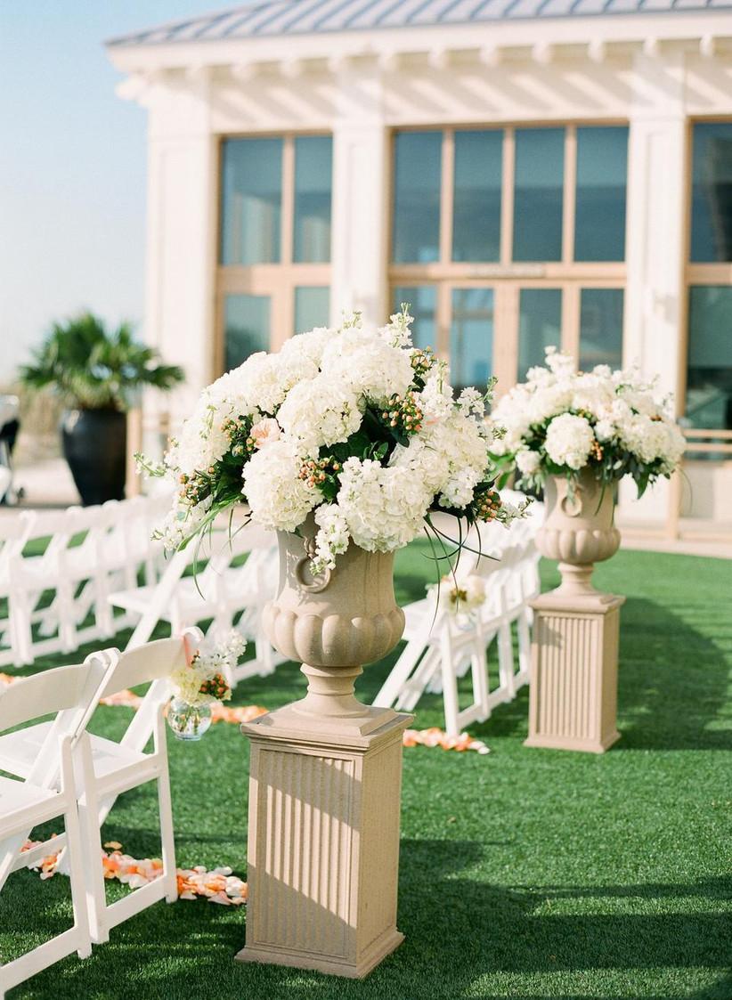 classic outdoor wedding aisle idea white hydrangea flower arrangements in stone urns on top of pillars