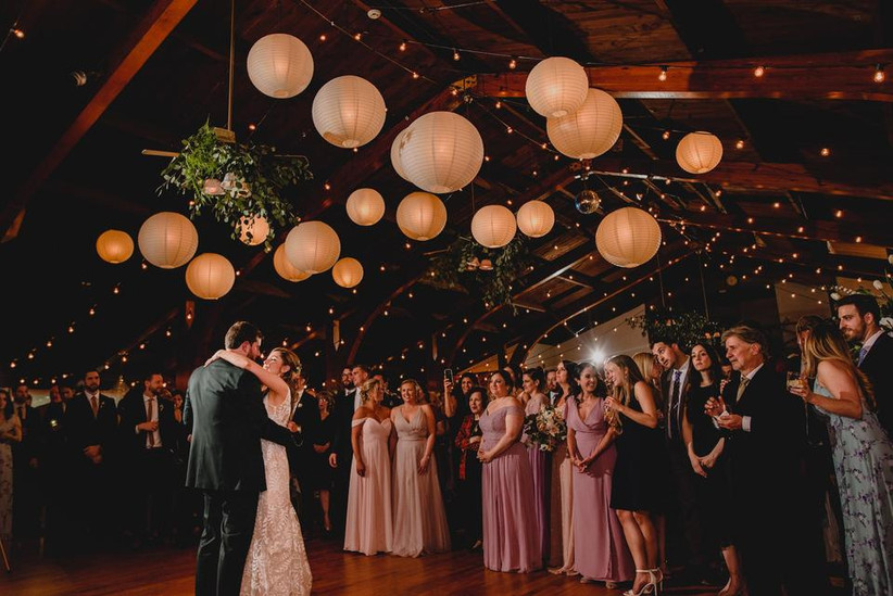 bride and groom dancing  under canopy of paper lanterns while wedding guests stand by and watch