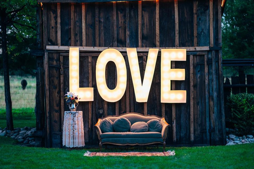 romantic wedding lighting idea giant marquee letters spelling LOVE on the side of a barn outdoor wedding reception lounge area