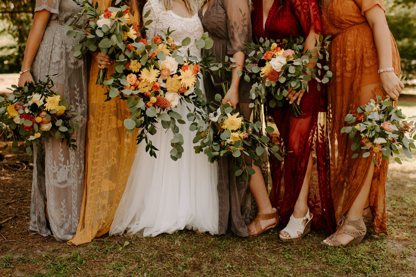 bridesmaids wearing fall colored dresses carrying bouquets of greenery and bright flowers