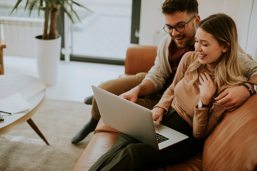 couple looking at laptop computer while sitting on a couch