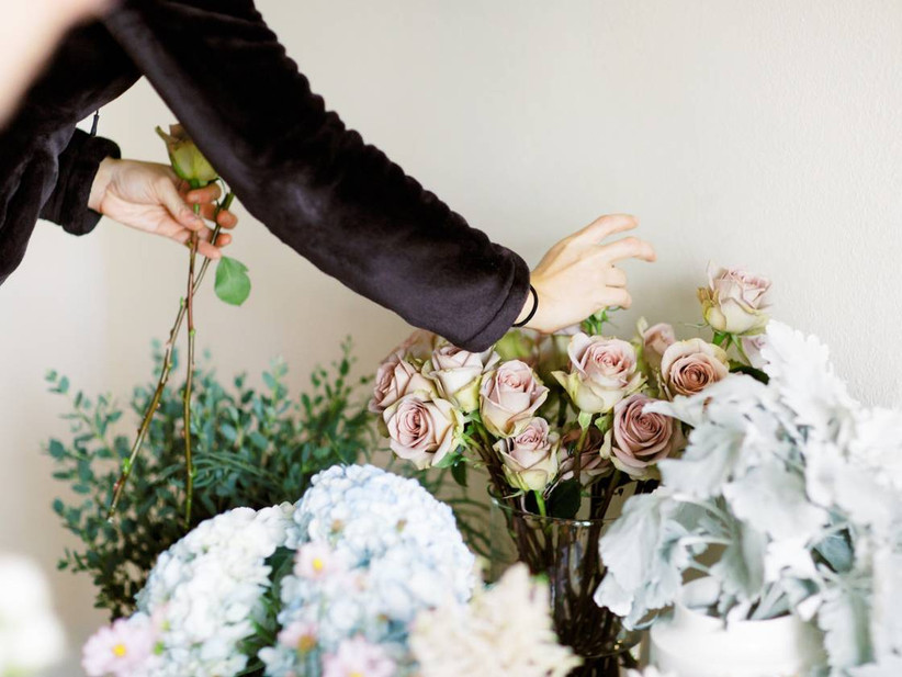 florist picking roses out of a glass vase
