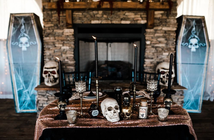 halloween themed wedding idea sweetheart table with faux skulls and tall candles