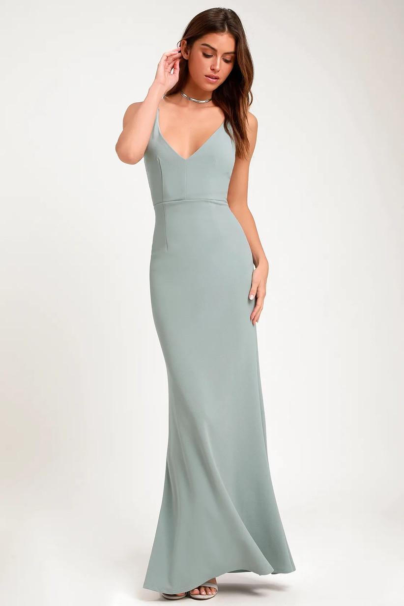 Model wearing minimalist pastel green trumpet bridesmaid dress with spaghetti straps