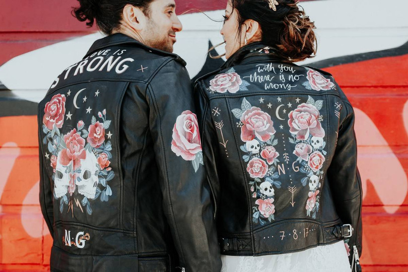 bride and groom stand with their backs to the camera wearing black leather jackets painted with roses and skulls