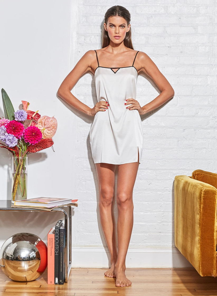 Model wearing short white silk slip with black trim and straps