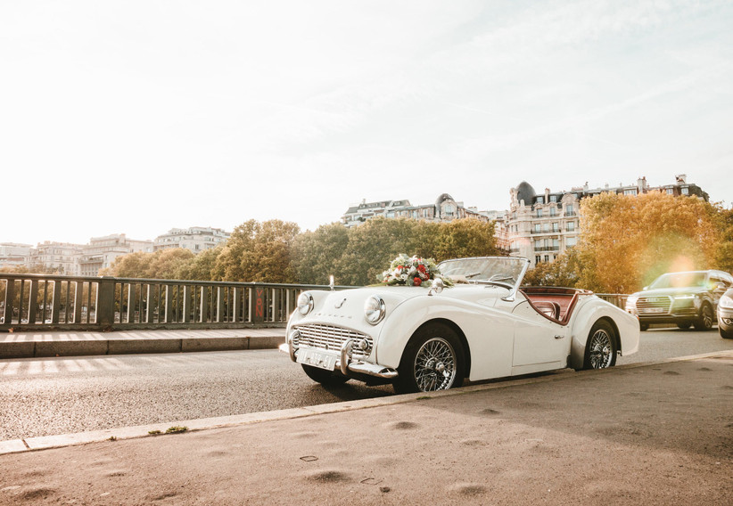 white vintage convertible is parked with paris scenery in the background
