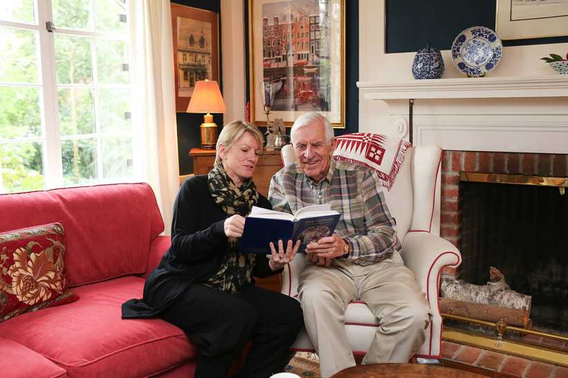 Older couple reading their memory book in a cozy living room