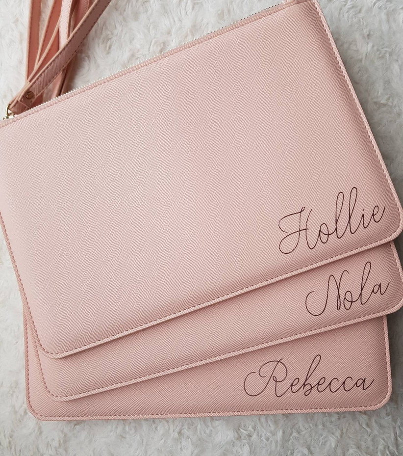 Three matching blush pink clutches personalized with bridesmaids' names in bottom right corner