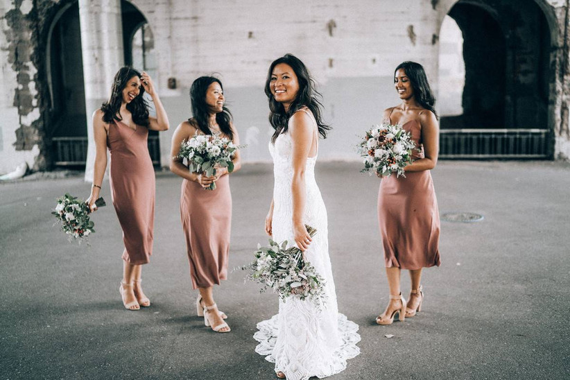 Bride smiles at the camera while three bridesmaids wearing mauve midi-length slip dresses stand next to her