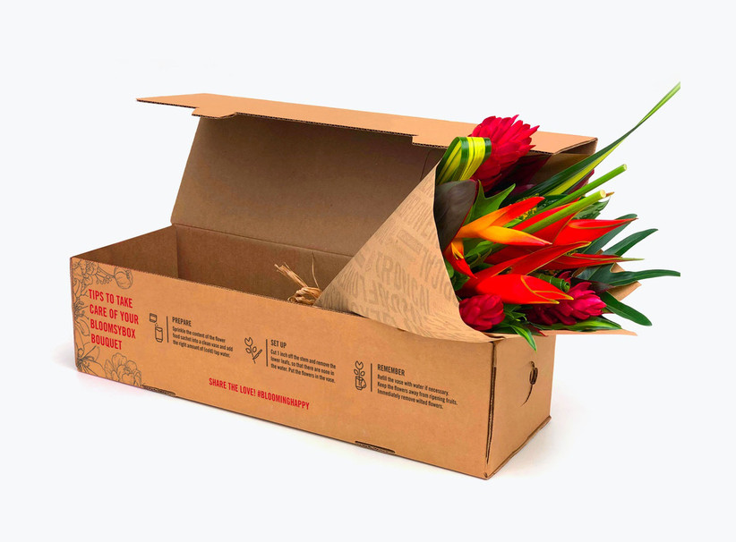 Tropical bouquet wrapped in brown paper positioned in a brown delivery box