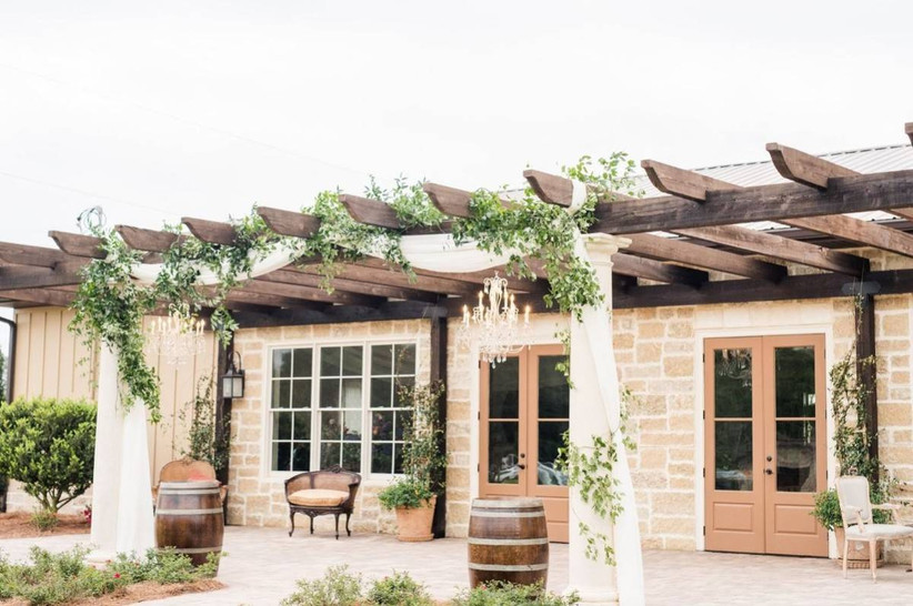 european-style brick courtyard with wooden pergola decorated in white fabric, vines, and chandelier